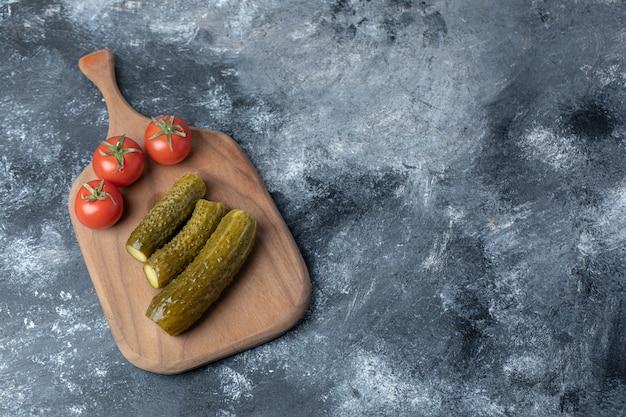 Un tagliere di legno di pomodori e cetrioli sottaceto.