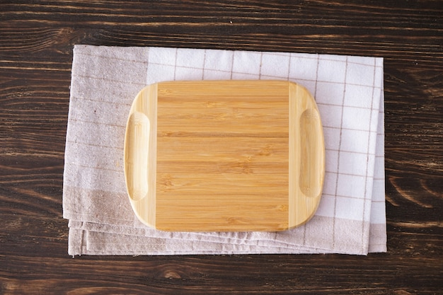 Wooden cutting board and towel on wooden background, flat lay. place for text.