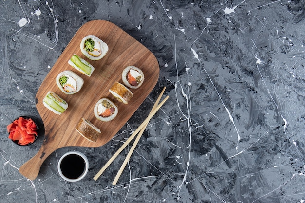 Wooden cutting board of various sushi rolls on marble table.
