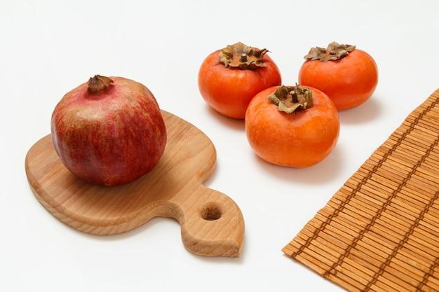 잘 익은 석류, 감 과일 및 흰색 표면에 대나무 냅킨 나무 도마