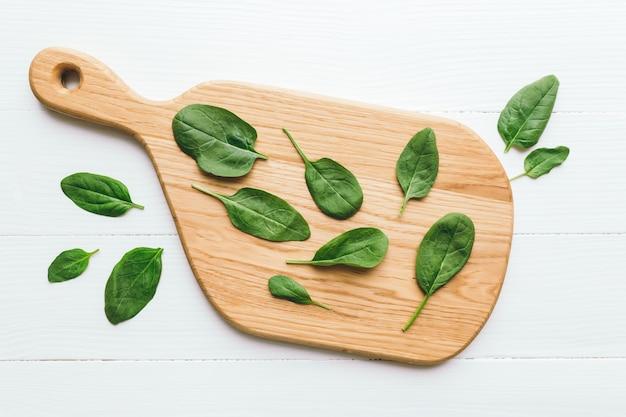 신선한 그린 샐러드와 나무 절단 보드 흰색 바탕에 시금치 잎. 채식 먹는 개념
