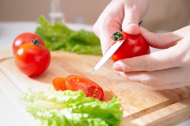 Деревянная разделочная доска со свежими травами, салатом и сырыми овощами на деревенской деревянной доске. приготовление фона. женские руки счищают с хвоста красный сочный помидор.