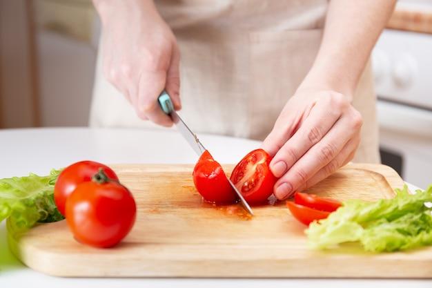 Деревянная разделочная доска со свежими травами, салатом и сырыми овощами на деревенской деревянной доске. приготовление фона. женские руки режут ножом сочный красный помидор.