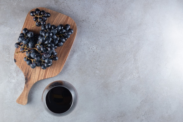 A wooden cutting board with grapes and glass cup of juice .