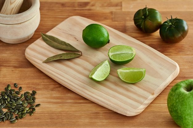 Wooden cutting board with limes and bay leaf on a kitchen table. minimalist photography. there are also some seeds some tomatoes, an apple and a mortar.