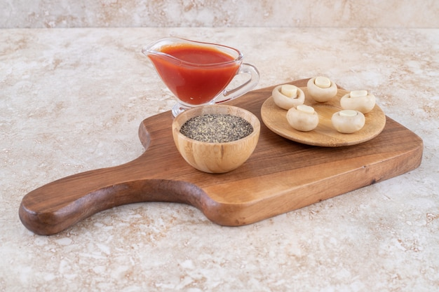 A wooden cutting board with mushrooms and ketchup