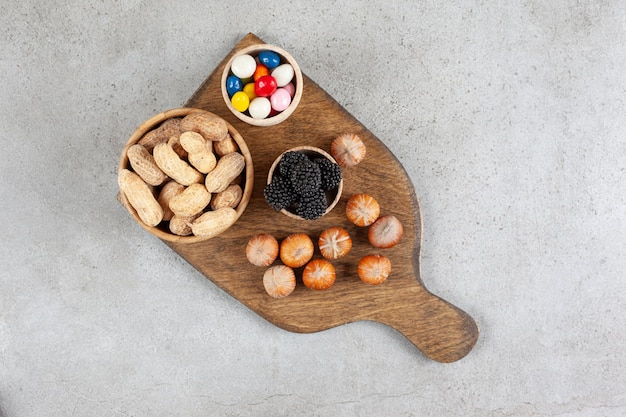 A wooden cutting board with nuts and blackberry