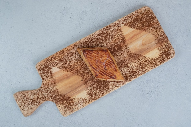 A wooden cutting board with powdered cacao and cookie