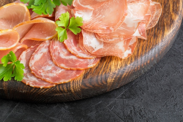 Деревянная разделочная доска с прошутто, беконом, салями и сосисками на деревянном фоне. мясное ассорти
