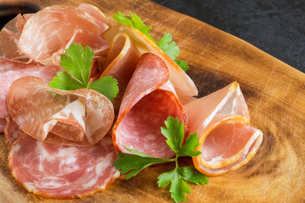 Wooden cutting board with prosciutto, bacon, salami and sausages on a wooden background. meat platter