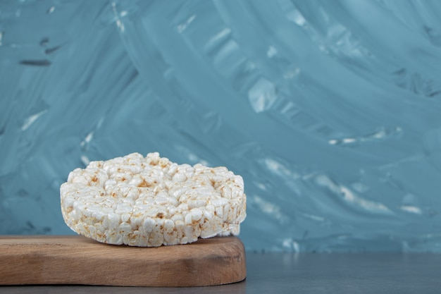 A wooden cutting board with puffed rice bread.