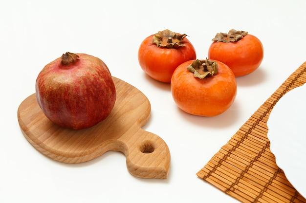 대나무 냅킨에 접시와 잘 익은 석류와 감 과일 나무 도마