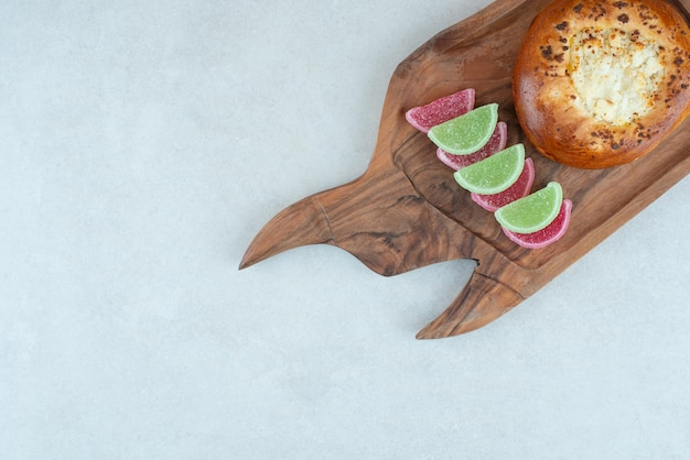 A wooden cutting board with round pastry and jelly candy .