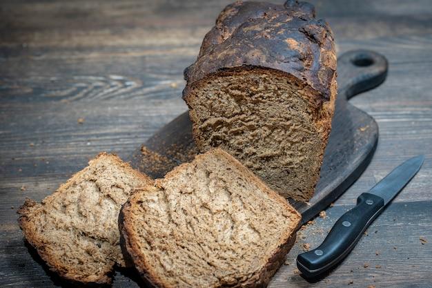木製のテーブルにスライスされたパンとナイフと木製のまな板、クローズアップ