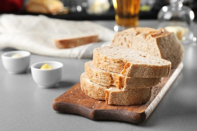 テーブルの上にビールブレッドのスライスしたパンと木製のまな板
