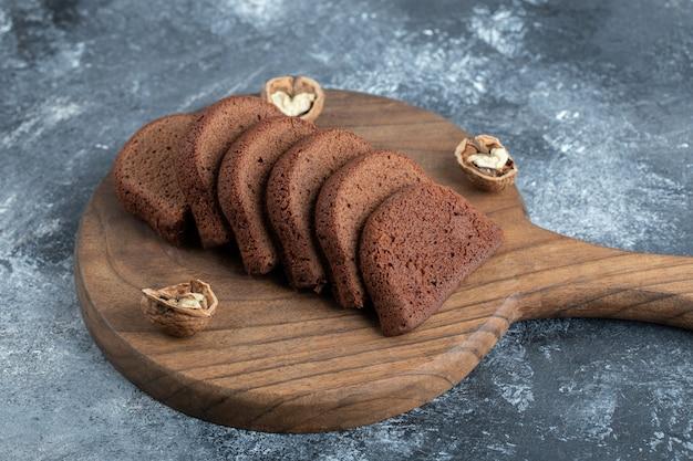 Un tagliere in legno con fette di pane e noci.