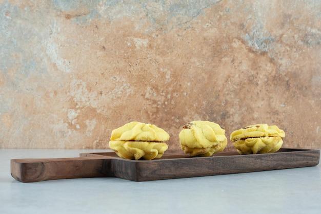 Un tagliere di legno con tre deliziosi biscotti sul tavolo bianco.