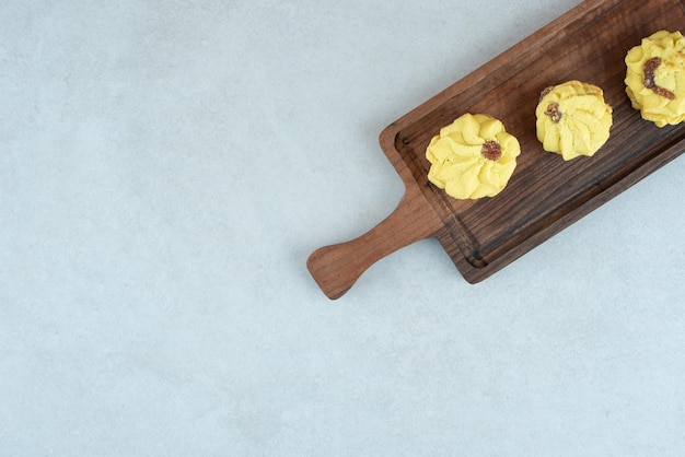 A wooden cutting board with three delicious cookies on white table.