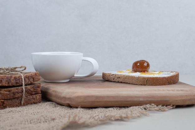 Un tagliere di legno con pane tostato e tazza di tè su tela di sacco.