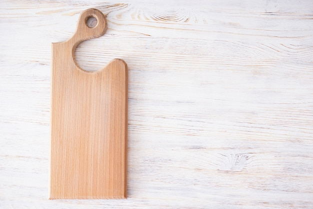 Wooden cutting board on wooden background, space for text. flat lay.