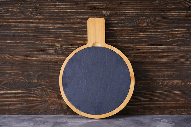 Wooden cutting board on a wooden background, space for text.