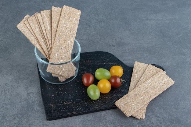 Un tagliere di legno scuro pieno di cereali croccanti di segale e pomodori colorati.