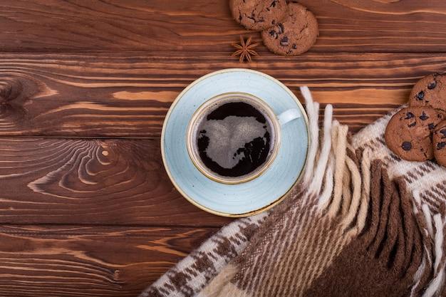 Деревянный темный стол с черным кофе, пледом и бисквитом. угол обзора сверху с копией пространства
