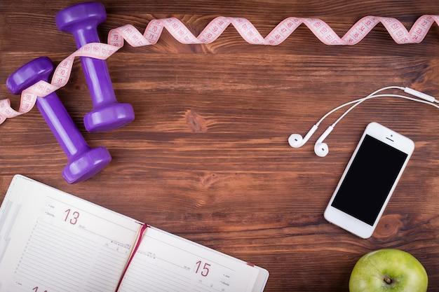 Деревянный темный стол с телефоном, наушниками, блокнотом, гантелями и зеленым яблоком. угол обзора сверху с копией пространства