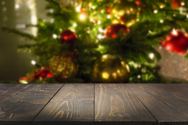 Wooden dark tabletop and blurred christmas tree bokeh. xmas background for display or montage your products.