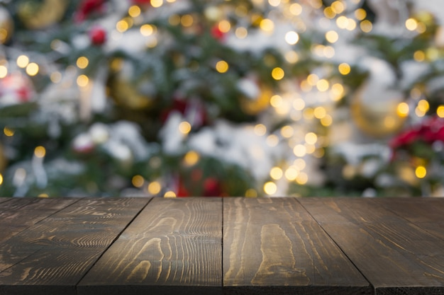Wooden dark tabletop and blurred christmas tree bokeh. xmas.