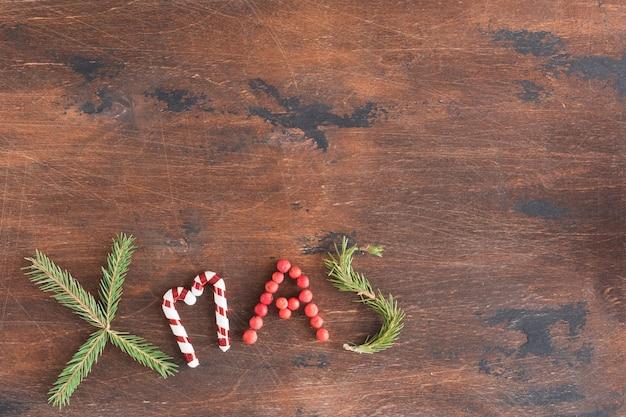 나무로 된 짙은 빈티지 크리스마스 또는 새해 배경, 겨울 시즌 장식으로 만든 보드의 xmas 텍스트, 텍스트 복사 공간, 위쪽 전망 및 평평한 레이아웃