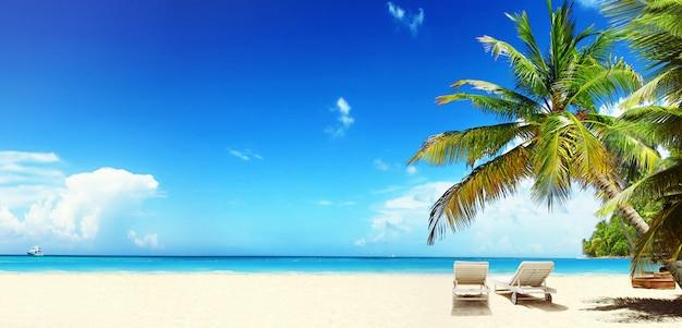 Деревянные шезлонги на песчаном пляже у моря. праздничный фон.