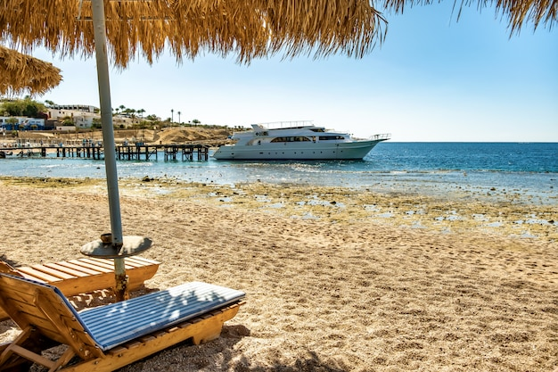 Wooden deck chairs under rough straw sun umbrella on sea beach and big white yacht ship in water near shore on sunny summer day.