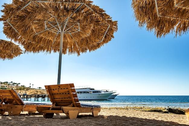 Деревянные шезлонги под грубым соломенным зонтиком от солнца на морском пляже и большой белый яхтенный корабль в воде возле берега в солнечный летний день.