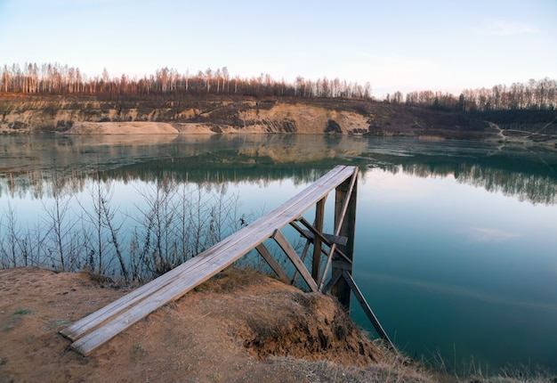 Wooden deck for diving on the shore of a sand quarry.