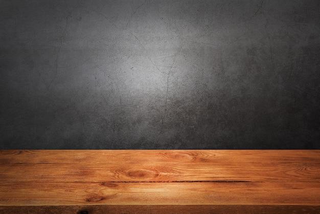 灰色のグランジの壁に木製のデッキテーブル。