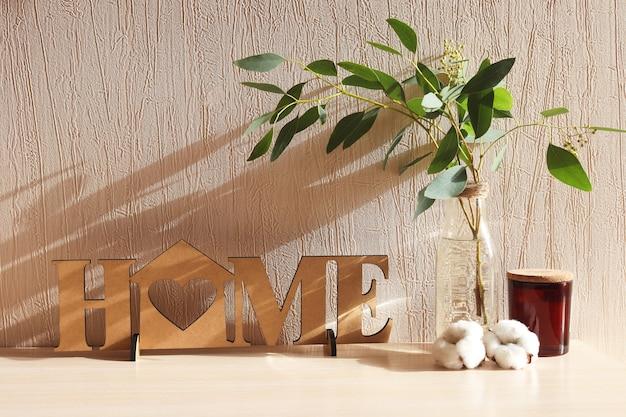 文字が付いている木の装飾ユーカリの小枝が付いている家の花瓶 Premium写真