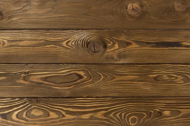 テキストのための場所と木製の装飾的な背景。結び目と穴、抽象的なテクスチャーを持つミディアムライトブラウンカラマツボード。家の装飾のための天然素材の概念。