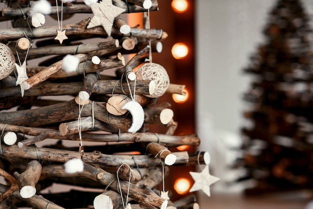 Wooden decorative chrismas tree with hand made toys. stylish christmas interior decorated in rustic style.