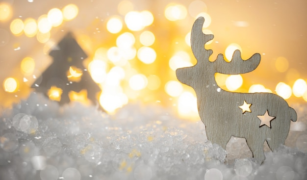 Wooden deer and christmas tree decorations in a snowdrift of snow against the background of golden bokeh.
