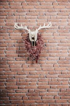 Деревянный олень висит на стене, украшенной рождественскими гирляндами. вертикальное изображение
