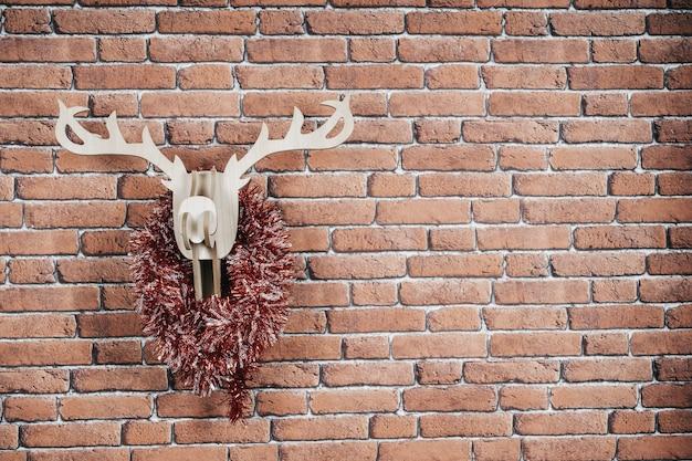 Деревянный олень висит на стене, украшенной рождественскими гирляндами