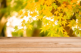 Wooden desk tabletop with blurred leaf nature background