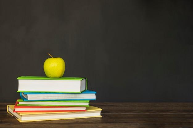 Scrivania in legno con libri e mela