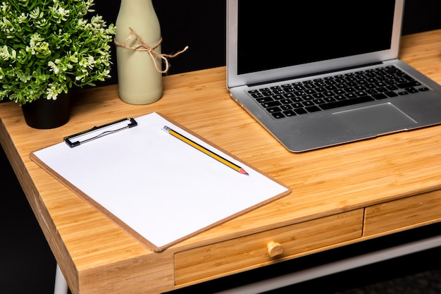 Wooden desk with clipboard and laptop
