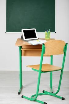 칠판 배경에 수업 시간에 문구류와 태블릿이 있는 나무 책상