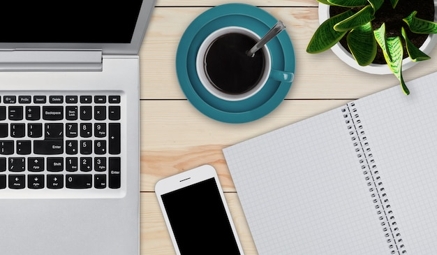 Wooden desktop with objects needed for work. modern laptop, smartphone, cup of coffee and notepad with blank sheets laying at wooden table. home workspace. education or business concept. devices
