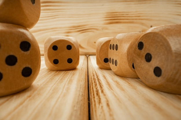 Wooden dice tossed on wooden background close up photo