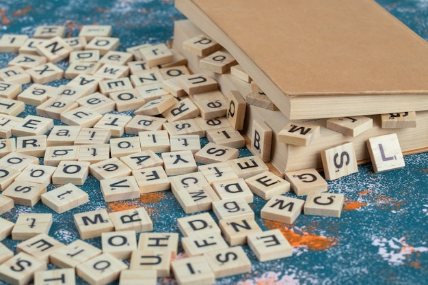 Wooden dice with letters on them between the pages of a book.