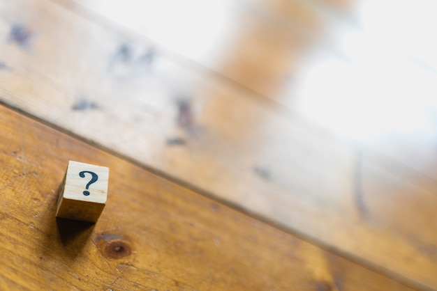 Wooden dice with question mark and doubt.